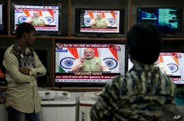 People watch Indian Prime Minister Narendra Modi addressing the nation, on television in Hyderabad, India, Dec. 31, 2016.