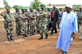 Mali's President Ibrahim Boubacar Keita, right, reviews troops in Kati, near Bamako, after visiting soldiers injured in an attack on their camp in northern Mali earlier in the week that left 11 other soldiers dead, Aug. 6, 2015.
