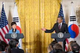 President Barack Obama gestures toward South Korean President Park Geun-hye during their joint news conference in the East Room of the White House in Washington, Oct. 16, 2015.