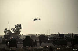 FILE - A helicopter prowls the perimeter of the Qayyarah military base, south of Mosul, Oct. 18, 2016.