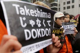 FILE - South Korean high school students stage a rally against Japan's Takeshima Day in front of the Japanese Embassy in Seoul, South Korea, Feb. 22, 2017.