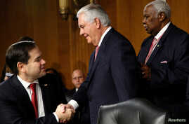 FILE - Rex Tillerson (C), the former chairman and chief executive officer of Exxon Mobil, shakes hands with U.S. Senator Marco Rubio (R-FL) as he arrives for a Senate Foreign Relations Committee confirmation hearing to become U.S. Secretary of State ...
