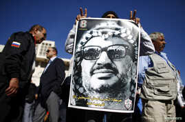A man holds a poster depicting late Palestinian leader Yasser Arafat during a rally in Bethlehem, West Bank, November 29, 2012.