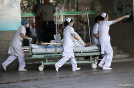 Medical personnel transport a victim of a factory explosion, at a hospital in Kunshan, Jiangsu province, August 2, 2014. An explosion killed at least 65 people and injured more than 120 at a factory in China that makes wheels for U.S. carmakers, incl