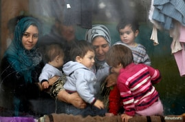Syrian refugees look through a window inside a refugee centre as they wait for a distribution of humanitarian aid by volunteers of the Bulgarian Red Cross in Sofia.