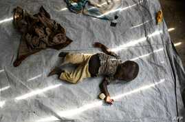 Newly arrived refugee boy from the Democratic Republic of Congo (DRC) sleeps in a makeshift shelter before their registration at Kyangwali Refugee Settlement in Kyangwali, western Uganda, Dec. 10, 2018.
