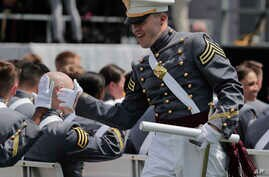 A West Point cadet gets a high five from a friend after receiving his diploma during graduation ceremonies at the United States Military Academy, Saturday, May 26, 2018, in West Point, N.Y.