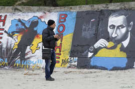 A man looks at a graffiti produced to support the territorial integrity of Ukraine and to protest Russia's annexation of the Black Sea peninsula of Crimea in Odessa, April 7, 2014.