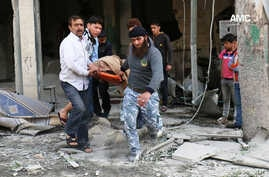 This photo provided by the anti-government activist group Aleppo Media Center (AMC), an anti-Bashar Assad activist group, which has been authenticated based on its contents and other AP reporting, shows Syrian men carrying a covered dead body after a