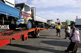 FILE - Trucks laden with goods headed for Zimbabwe are seen near the Beitbride border post between South Africa and Zimbabwe, in Musina, South Africa, March 28, 2008.