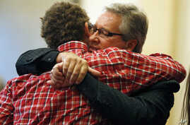 Randy Scroggins, pastor at New Beginnings Church of God, right, embraces Mathew Downing, who was spared during a shooting at Umpqua Community College, during a church service at New Beginnings in Roseburg, Ore., Oct. 4, 2015.
