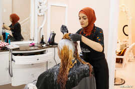 Huda Quhshi, owner and cosmetologist at the Le'Jemalik Salon and Boutique, dyes the hair of a woman ahead of the Eid al-Fitr Islamic holiday in Brooklyn, New York, June 21, 2017.