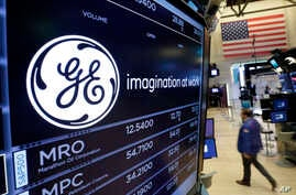 The General Electric logo appears above a trading post on the floor of the New York Stock Exchange, Monday, June 12, 2017. GE said Jeff Immelt is stepping down as CEO and John Flannery will take over the post in August.