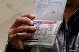 FILE - A member of the Al Murisi family, Yemeni nationals who were denied entry into the U.S. last week because of the recent travel ban, shows the cancelled visa in their passport from their failed entry to reporters.