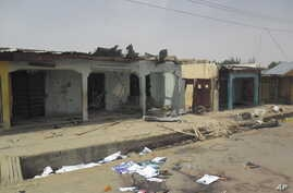 Bloodstains seen on the street and damage buildings following a suicide bomb explosion at a World cup viewing centre in Damaturu, Nigeria, Wednesday, June 18, 2014. Police say 14 people were known to have died in the bombing of an outdoor World Cup v
