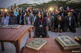 New Somali parliamentarians pray during an inauguration ceremony for members of Somalia's first parliament in 20 years in Mogadishu, August 20, 2012.