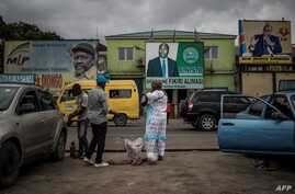 A woman sells beverages to driving school tutors as electoral posters are seen in the background in Kinshasa, Democratic Republic of the Congo, Dec. 17, 2018.