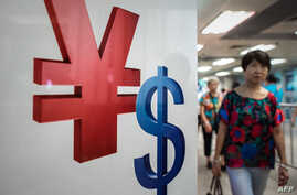 A woman walks past a yuan (L) and a US dollar (R) currency sign in Hong Kong on August 13, 2015.
