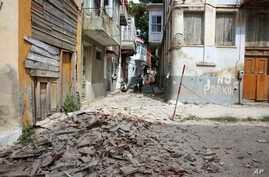 People look at  the debris of a damaged building after an earthquake in the village of Plomari on the northeastern Greek island of Lesbos, June 12, 2017.
