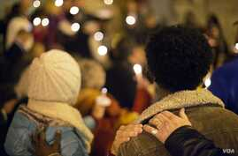 """FILE - Community members place hands on each others shoulders during a candlelit vigil in support of the """"safe harbor"""" legislation for child victims of human trafficking, Dec. 11, 2014, in Atlanta."""
