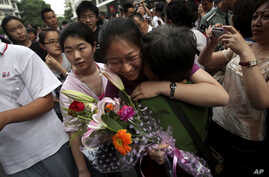 """A Chinese student is greeted by a relative after attending the end of the annual college entrance examinations, in Beijing, China, Tuesday, June 8, 2010. Each year, about 10 million high school seniors across China take the """"gaokao"""" -- the exam that"""