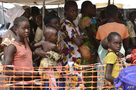 FILE - Internally-displaced people wait in line for medical attention at the 'Medecins sans Frontieres' (MSF) hospital based in the IDP camp near the international airport in Bangui, Dec. 23, 2013.