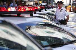 FILE - A police officer stands in a row of police cars parked in Times Square in New York.