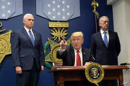 FILE - President Donald Trump, center, signed two executive actions at the Pentagon in Washington, Jan. 27, 2017, with Vice President Mike Pence, left, and Defense Secretary James Mattis at his side.