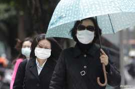 Pedestrians wearing medical masks walk on the street outside National Taiwan University Hospital in Taipei, April 26, 2013. A 53-year-old Taiwan businessman contracted the H7N9 strain of bird flu while travelling in China, the first reported case out