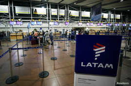 Passengers wait to check in for their flights at the departures area of Latam airlines inside the international airport in Santiago, Chile, Aug. 16, 2018.