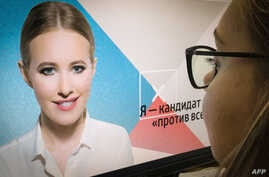 A journalist looks at a computer screen displaying Ksenia Sobchak's campaign web page, in Moscow, Russia, Oct. 19, 2017.