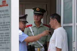 A Chinese police officer points as he speaks to a Chinese man held at a security checkpoint on Tiananmen Square in Beijing Wednesday, June 4, 2014.