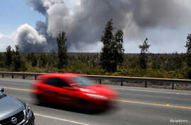 As a car dashes by, an ash plume rises from the Halemaumau Crater on Kilauea's summit, near Volcano, Hawaii, May 25, 2018.