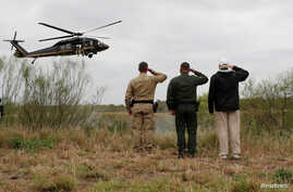 President Donald Trump salutes a U.S. Border Patrol helicopter with U.S. Border Patrol agents as it flies over the Rio Grande River during his visit to the U.S.- Mexico border in Mission, Texas, Jan. 10, 2019.