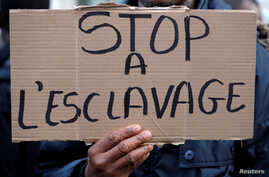 """A man holds a placard with the message """"Stop slavery"""" as he attends a protest against slavery in Libya outside the Libyan Embassy in Paris, France, Nov. 24, 2017."""