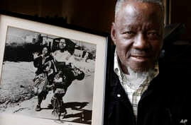 FILE - South African photographer Sam Nzima poses with his iconic photo showing 13-year-old Hector Pieterson being carried after being shot dead by apartheid police during the 1976 Soweto uprising, in Pretoria, April 27, 2011.