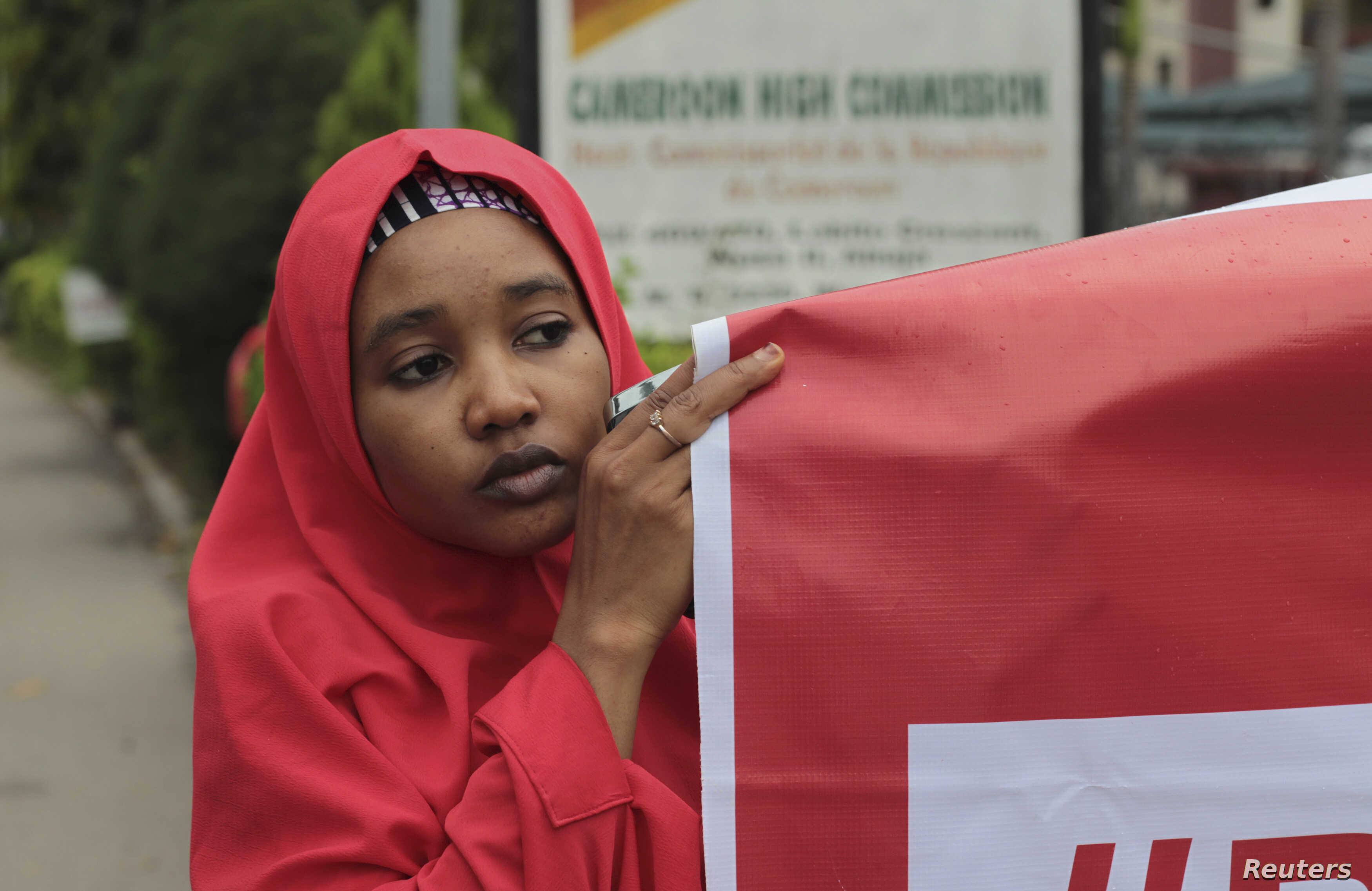 """FILE - A campaigner from """"#Bring Back Our Girls"""" hold a banner during a rally calling for the release of the Chibok school girls who were abducted by the Boko Haram militants, outside the Cameroon Embassy in Abuja."""