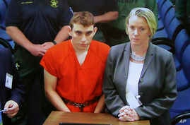 A video monitor shows school shooting suspect Nikolas Cruz, left, making an appearance before Judge Kim Theresa Mollica in Broward County Court, Thursday, Feb. 15, 2018, in Fort Lauderdale, Florida.