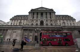 FILE - People hold umbrellas to shelter from the rain as they walk past the Bank of England in London, Aug. 4, 2011.