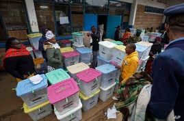 Electoral workers stand by ballot boxes stacked up at a collection center in Nairobi, Aug. 9, 2017.