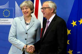 British Prime Minister Theresa May is greeted by European Commission President Jean-Claude Juncker before a meeting at EU headquarters in Brussels, Dec. 8, 2017. May and Juncker met early Friday morning following crucial overnight talks on the issue