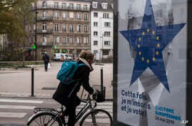 FILE - A cyclist rides past of campaign poster by the Strasbourg municipality for the upcoming European elections in Strasbourg, eastern France, Nov.22, 2018.