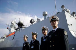 FILE - In this Dec. 7, 2016, photo, Chinese Navy officials stand in front of the ship Daqing, in San Diego.