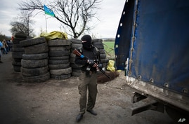 A pro-Russia gunman is seen at a checkpoint, after a shootout near Slovyansk, eastern Ukraine, April 20, 2014.