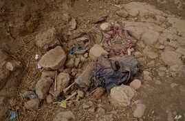 FILE - Human remains lie on the ground in a ravine near Badoush, northern Iraq, Sept. 6, 2017. Iraqi military investigators have identified two mass graves in the area that they say contain the remains of at least 500 people, executed by Islamic Stat