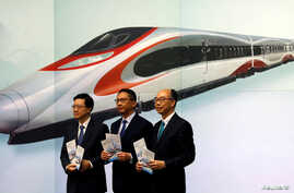 Secretary for Security John Lee, from left, Secretary for Justice Rimsky Yuen and Secretary for Transport & Housing Frank Chan pose at a news conference on arrangements at West Kowloon Terminus for the Guangzhou-Shenzhen-Hong Kong Express Rail Link i