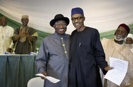 """Nigeria's President Goodluck Jonathan, center-left, and opposition candidate Gen. Muhammadu Buhari, center-right, hug and shake hands after signing a renewal of their pledge to hold peaceful """"free, fair, and credible"""" elections, at a hotel in the cap"""