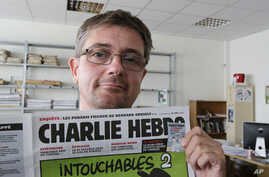 "FILE - Publishing director of the satiric weekly Charlie Hebdo, ""Charb,"" displays the front page of the newspaper, in Paris, Sept. 19, 2012."
