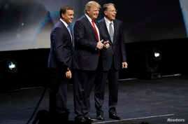 FILE - Republican presidential candidate Donald Trump is introduced by National Rifle Association executive director Chris W. Cox (L) and NRA executive vice president Wayne LaPierre (R), as Trump takes the stage to speak at the NRA convention, May 20