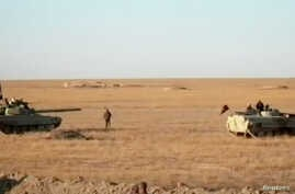 Armored vehicles take position in the middle of a desert near Syria border, Iraq in this still image taken from a video obtained by Reuters on Nov. 23, 2017. (Hashid Shaabi/Handout via Reuters TV)